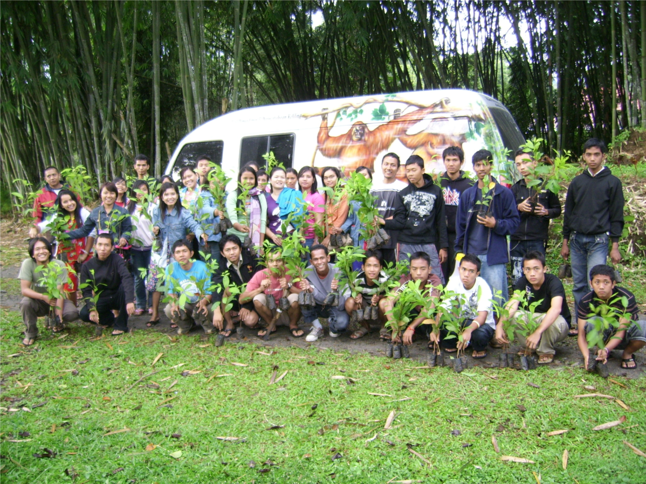 A group of people standing in front of an environmental education van with orangutans painted on it.