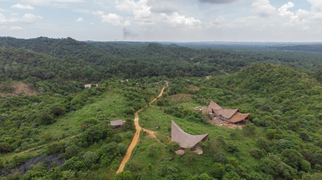 An aerial view of Leuser Nature School with its bamboo buildings surrounded by forest.