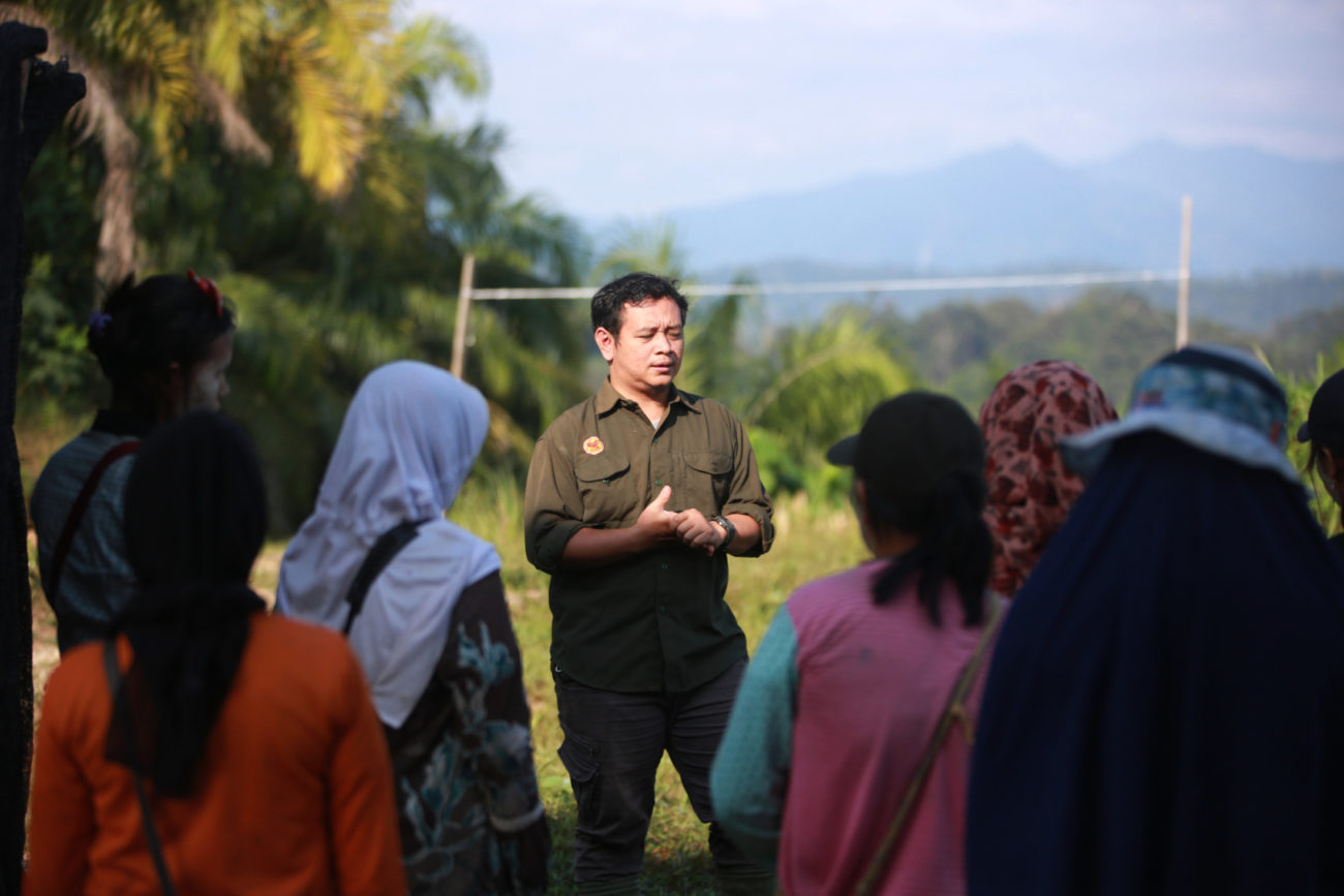 A man in uniform is talking to a group of people. They are outside and there is forest in the background.